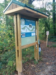 Trailhead kiosk showing map, historic photos, and timeline of greenway development.